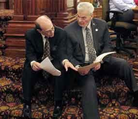 In this photo Kansas state Reps. Steve Brunk, left, a Wichita Republican, and Arlen Siegfreid, right, an Olathe Republican, confer during a Statehouse debate in Topeka, Kan., prior to passage of the Second Amendment Protection Act. (AP Image)