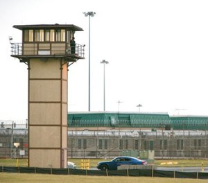 In this Feb. 1, 2017, file photo, a prison guard stands on a tower during a hostage situation at James T. Vaughn Correctional Center in Smyrna, Del. (Suchat Pederson/The News Journal via AP)