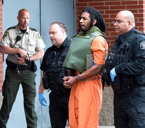 In this May 10, 2017, file photo, Wesley Correa-Carmenaty is led into the Woodbury County Jail in Sioux City, Iowa. Prosecutors say the man charged with killing a sheriff's deputy and wounding another while escaping from an Iowa jail will plead guilty. (Tim Hynds/Sioux City Journal via AP, File)