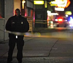In this Wednesday, Nov. 6, 2013 file photo, a Detroit Police officer stands guard behind barrier tape at the scene of a shooting which left three dead at a barbershop in Detroit. (AP Image)