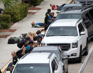People take cover outside Fort Lauderdale–Hollywood International Airport, Friday, Jan. 6, 2017, in Fort Lauderdale, Fla., after a shooter opened fire inside a terminal of the airport, killing several people and wounding others before being taken into custody.