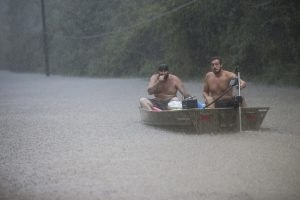 Image: A pair of men get into a boat to float in to rescue a family trapped by floodwaters as rain from Tropical Depression Imelda inundated the area on Thursday, Sept. 19, 2019, near Patton Village, Texas.