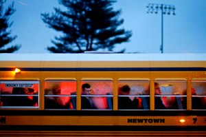 People arrive on a school bus at Newtown High School for a memorial vigil attended by President Barack Obama for the victims of the Sandy Hook Elementary School shooting in Newtown, Conn.