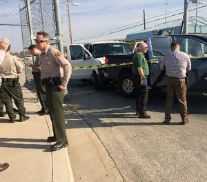 This image provided by Ray Pruitt with the Kern County Sheriffs Office shows officers looking at a pickup truck after a white prison van crashed into it at the gates of the Lerdo Pre-Trial Facility near Bakersfield, Calif., on Weds., March 2, 2016.