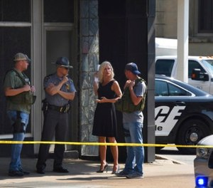 Officials consult near the crime scene at the Huntington Bank, next to the Courthouse in Steubenville, Ohio, Monday Aug. 21, 2017, after Jefferson County Judge Joseph Bruzzese Jr. was ambushed and shot while walking to work early Monday morning.