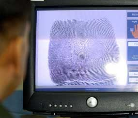 U.S. Bureau of Customs and Border Protection senior agent Arnie Villarreal looks at a fingerprint on the new Automated Fingerprint Identification System during a demonstration at the Brown Field Station along the U.S-Mexico border. (AP Image)