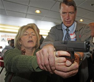 Christine Caldwell, left, receives firearms training with a 9mm Glock from personal defense instructor Jim McCarthy during concealed weapons training for 200 Utah teachers. (AP Image)