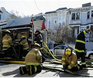 San Francisco Firefighters work after a fire damaged buildings. Fire officials the fire destroyed one house, damaged two others and left one firefighter with minor burns.