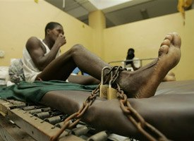 An inmate is padlocked to a bed in the emergency room of the General Hospital of Port-au-Prince, Haiti. (AP Photo/Ariana Cubillos)