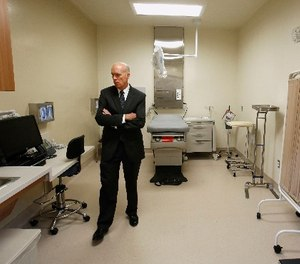 In this June 25, 2013 file photo , David Culberson, chief executive officer of San Joaquin General Hospital, looks over one of the patient care rooms while touring the new California Correctional Health Care Facility in Stockton, Calif.