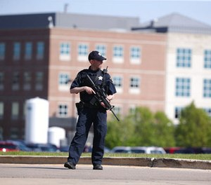 A Kane County police officer monitors the scene at Northwestern Medicine Delnor Hospital in Geneva, Ill., during a lockdown after a jail inmate being treated there managed to take a correctional officer's gun in the facility and hold an employee hostage, Saturday, May 13, 2017.