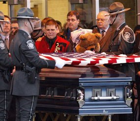 A Pennsylvania State Police honor guard folds the flag over the casket containing the remains of Pennsylvania State Trooper Paul G. Richey during a memorial service. Richey, a 16-year veteran, was killed by a gunman lying in wait while answering a domestic call.