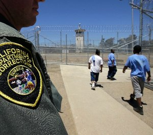 In this photo taken June 20, 2018, inmates pass a Correctional Officer as they leave an exercise yard at the California Medical Facility in Vacaville, Calif. (AP Photo/Rich Pedroncelli)