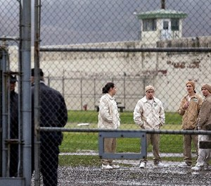 In this file photo taken Jan. 28, 2016, inmates mingle in a recreation yard in view of COs, left, at the Monroe Correctional Complex in Monroe, Wash.