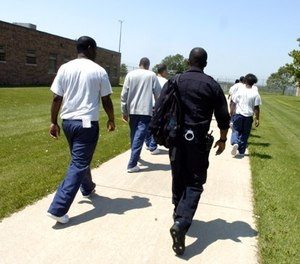 Youths, escorted by a youth supervisor, walk to their classroom building at the Illinois Department of Juvenile Justice Center in Joliet. (Photo/Antonio Perez)