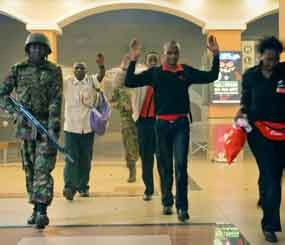 Civilians who had been hiding during gunbattles hold their hands in the air as a precautionary measure before being searched by armed police leading them to safety, inside the Westgate Mall in Nairobi, Kenya on Sept. 21. (AP Image)