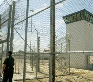 A correctional officer walks near a gate, which is one of two entrances into Kern Valley State Prison Tuesday, June 14, 2005, in Delano, Calif. (AP Photo/Ric Francis)