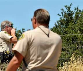 The Santa Barbara County Sheriff Officials Buddy Allain, left, and B. Collins, tell people to evacuate due to the La Brea Fire burning in the hills above Tepusquet Canyon Road East of Santa Maria, Calif. (AP Photo/Phil Klein)
