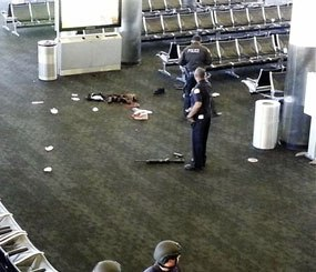 In this Nov. 1, 2013 file photo provided to the AP, which has been authenticated based on its contents and other AP reporting, police officers stand near a weapon at the Los Angeles International Airport after a gunman opened fire in the terminal, killing one person and wounding several others. (AP Image)
