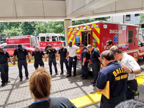 Dallas Fire-Rescue Chaplain Ray Schufford leading prayer for a safe drive home and seamless recovery for An.