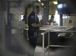 A corrections officer mans a security post in an enhanced supervision housing unit on Rikers Island in New York, Thursday, March 12, 2015. (AP Photo/Seth Wenig)