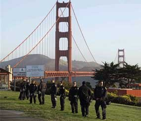 California Highway Patrol members stand watch at the Golden Gate Bridge in preparation for possible May Day protests in San Francisco, Tuesday, April 1, 2012.  Protesters had backed away from a call to block the bridge. But scores of California Highway Patrol officers nonetheless lined the span and gathered around the toll plaza this morning.