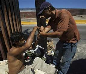 Drug addicts help each other get high at a street corner near the international border in Tijuana, Mexico Tuesday, Aug. 25, 2009. Mexico now has some of the most liberal laws in the world for drug users after eliminating jail time for tiny amounts of marijuana, cocaine and even heroin, LSD and methamphetamine. (AP Photo/Guillermo Arias)