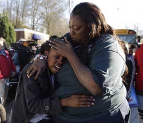 A woman comforts a child after after a shooting at an Price Middle school in Atlanta on Thursday, Jan. 31, 2013. A 14-year-old boy was wounded outside the school Thursday afternoon and a fellow student was in custody as a suspect, authorities said. No other students were hurt. (AP Image)