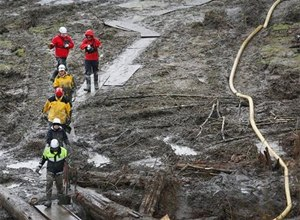 Search and rescue teams walk through a field of mud on a path of plywood at the west side of the mudslide on Highway 530 near mile marker 37 in Arlington, Wash. (AP Photo/Rick Wilking, Pool)