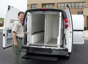 Capt. Steve Snow, director of security at the Frederick County Adult Detention Center, on Monday stands beside the 2013 Chevy van used to transport prisoners. The van has two compartments in the back that can hold six and four people and one compartment that can hold two people. (Photo Sam Yu/Frederick News-Post)
