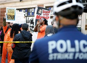 Several dozen supporters of Mumia Abu-Jamal, some dressed in orange, prison-like jumpsuits, protest near the Re-victimization Relief Act bill signing Tuesday Oct. 21, 2014, in Philadelphia. (AP Photo/Michael Sisak)