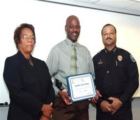 In this 2008 image provided by the Jackson, Miss. Police, Detective Eric Smith, center, flanked by Chief Rebecca Coleman, left, and Assistant Chief Lee Vance accepts the Certificate of Commendation.