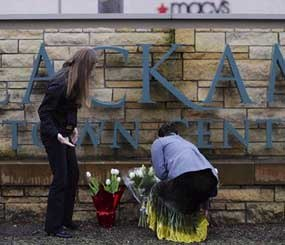 Leslie King, right and Tenille Beseda place flowers Wednesday Dec. 12, 2012, at the entrance to the scene of a multiple shooting yesterday at Clackamas Town Center Mall in Portland, Ore.  A gunman who opened fire on shoppers at the mall had no connection to the two people he fatally shot and wanted to kill as many people as possible, police said Wednesday.