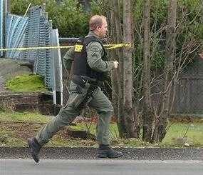 A Pierce County Sheriff deputy runs to the site where four police officers killed in an ambush at the Forza Coffee Co. near Parkland, Wash., on Sunday, November 29, 2009. Pierce County Sheriff's spokesman Ed Troyer told The News Tribune in Tacoma one or two gunmen burst into the Forza Coffee Co. and shot the four uniformed officers as they were working on their laptop computers, then fled the scene. (AP Photo)