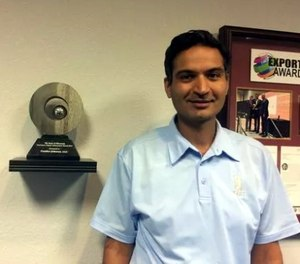 Gautam Malik, chief operating officer, stands next to the 2015 Governor's Export Achievement Award. (Photo/USA Today)