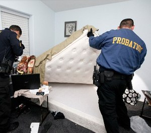 In this photo taken Friday, March 6, 2013, San Bernardino County Probation officers search a parolee room for drugs and arms during a night probation compliance sweep in Apple Valley, Calif.