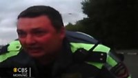 Russian police officer clings to hood of car