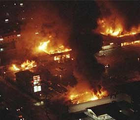 This April 29, 1992 file photo shows several buildings in a Boys Market shopping center fully engulfed in flames before firefighters can arrive as rioting erupted in South-Central Los Angeles. The acquittal of four police officers in the Rodney King case sparked rioting that spread across the city and into neighboring suburbs. Cars were demolished and homes and businesses were burned. Before order was restored, 55 people were dead, 2,300 injured and more than 1,500 buildings were damaged or destroyed. (AP Photo/Reed Saxon, File)
