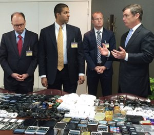 In this photo made available by the South Carolina Department of Corrections on Wednesday, April 6, 2016, their director, Bryan Stirling, right, showing hundreds of cellphones that were seized in a single raid from the Lee Correctional Institution, S.C. (Stephanie Givens, South Carolina Department of Corrections via AP)