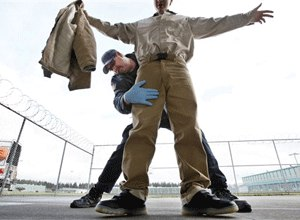 Correctional officer Ken Kleinworth frisks an inmate leaving a dining hall at the Washington Corrections Center, Thursday, Feb. 17, 2011, in Shelton, Wash. (AP Photo/Elaine Thompson)