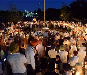 Sikh women and men hold candles during a prayer vigil at the Sikh Religious Society temple in Palatine, Il. on Monday, Aug. 6, 2012.  The vigil was held in memoriam of those killed and wounded in a  weekend Sikh temple shooting near Milwaukee. (AP photo / Daily Herald, Mark Welsh)