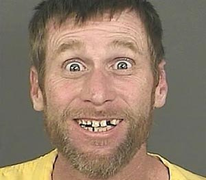 A Sept. 23, 2014 photo provided by the Denver District Attorney's Office shows Michael Whitington with a broad, toothy smile and eyes open wide after his Sept. 23, 2014 arrest in Denver.