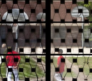 In this May 20, 2010, file photo some youths are seen playing basketball through bars on a window at the Wisconsin Department of Corrections Ethan Allen School in Wales, Wis.