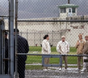 In this file photo taken Jan. 28, 2016, inmates mingle in a recreation yard in view of COs, left, at the Monroe Correctional Complex in Monroe, Wash. (AP Photo/Elaine Thompson, File)