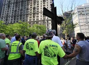 AP Photo/Mark Lennihan, File World Trade Center construction workers hold hands during a prayer at a ceremony for the September 11 cross,  in New York.