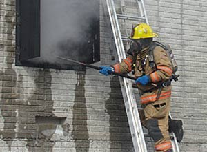Photo IAFFA firefighter conducts a second-story ventilation at a controlled fire duringthe firefighter safety and resource deployment study.