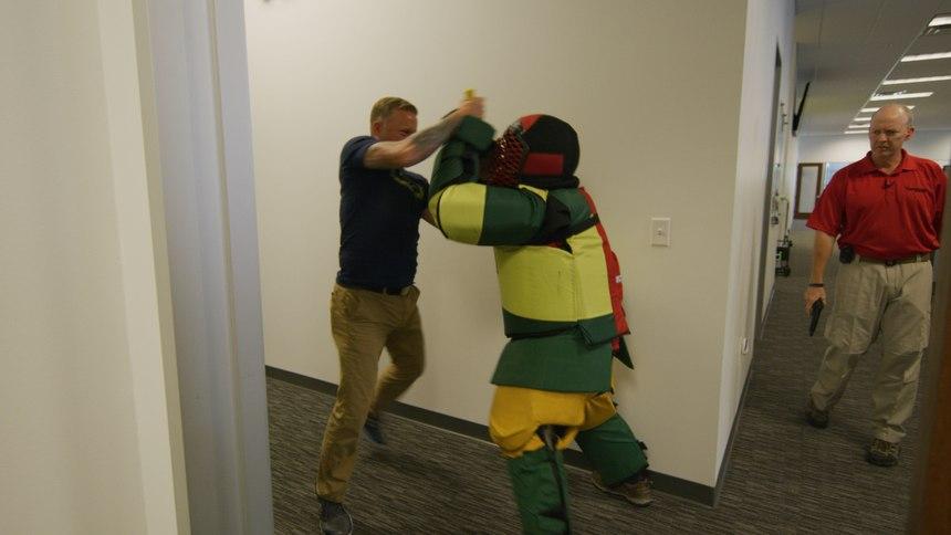 A participant practices defense moves against instructor Griffin.