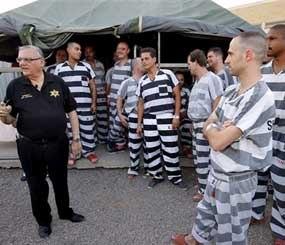 Inmates gather next to Maricopa County Sheriff Joe Arpaio as he walks through a Maricopa County Sheriff's Office jail called
