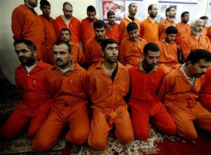 In this Dec. 2, 2010 file photo, handcuffed al-Qaida-linked suspects sit in the terrorist and organized crime department in Baghdad, Iraq. (AP Photo/Hadi Mizban, File)