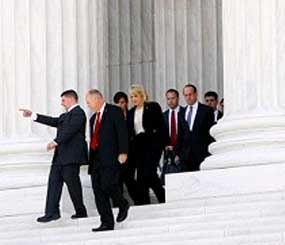 Arizona Gov. Jan Brewer, center, walks out after the Supreme Court in Washington, Wednesday, April 25, 2012, after the court's hearing on Arizona's